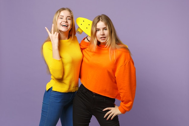 Two cheerful young blonde twins sisters girls in vivid clothes showing victory sign, holding yellow skateboard isolated on violet blue wall. people family lifestyle concept. .