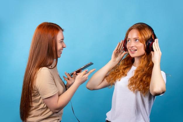 カジュアルな服装の2人の陽気な若い女性の友人。青い壁に隔離。人々のライフスタイルの概念携帯電話を使用して音楽のヘッドフォンを聞く。