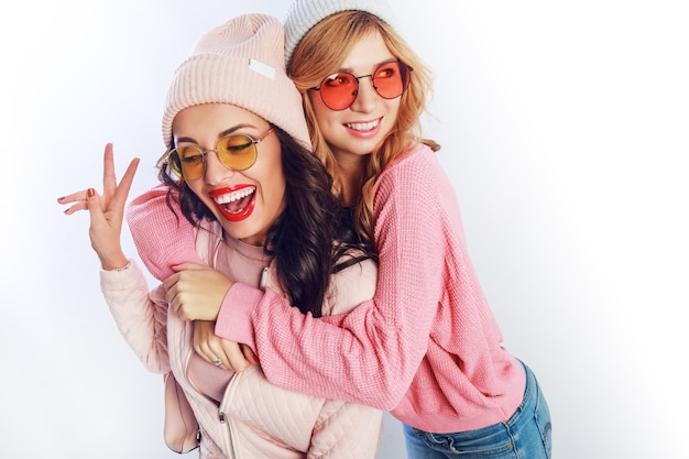 Two cheerful young friends in perfect mood having time together on white isolate background. positive girls wearing pink  cozy sweaters and pullover, trendy hat , cute glasses.