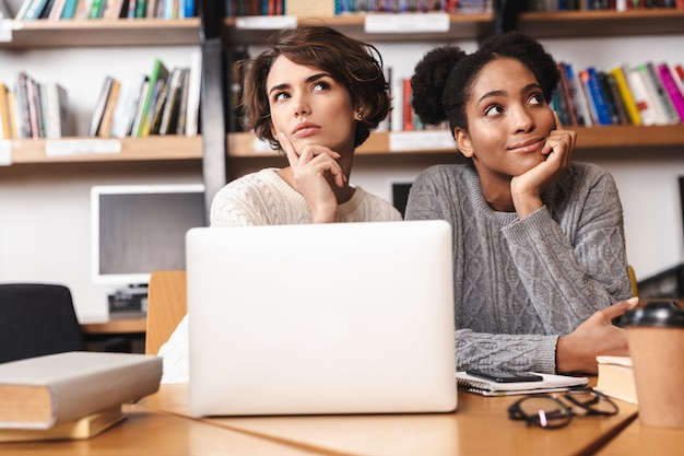 Две веселые молодые девушки-студенты учатся в библиотеке, сидя за столом с портативным компьютером