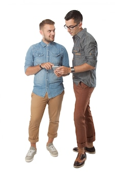 2つの陽気な若い男が携帯電話で何かを話し合い、笑顔