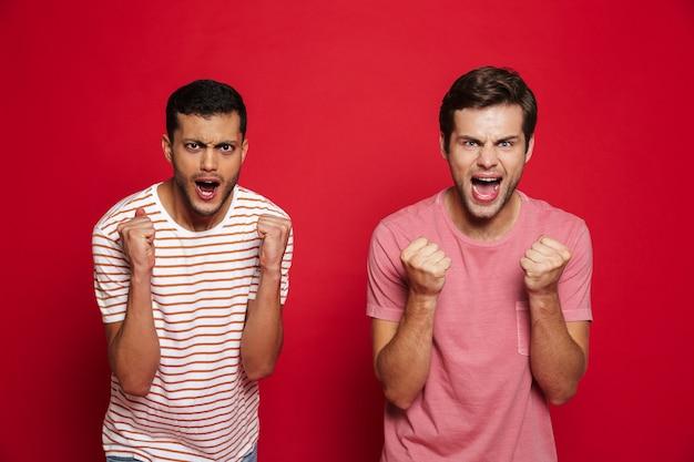 Двое веселых молодых людей, стоящих изолированно над красной стеной, празднуют успех