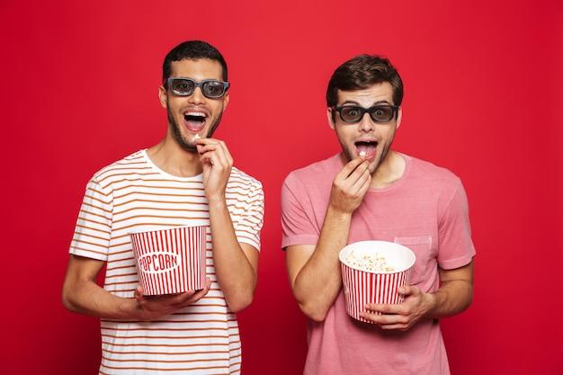 Двое веселых молодых людей стоят изолированно над красной стеной и едят попкорн в 3d-очках