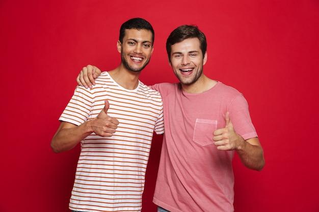 Два веселых молодых человека, стоящие изолированно над красной стеной и показывая большие пальцы руки вверх