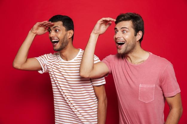 Двое веселых молодых людей стоят изолированно над красной стеной и смотрят вдаль