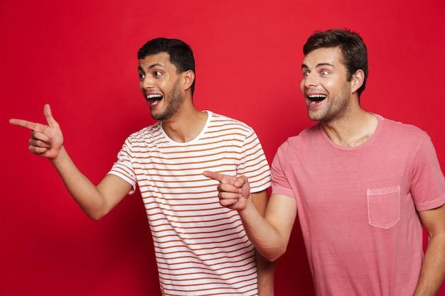 Два веселых молодых человека стоя изолированно над красной стеной, указывая на место для копирования