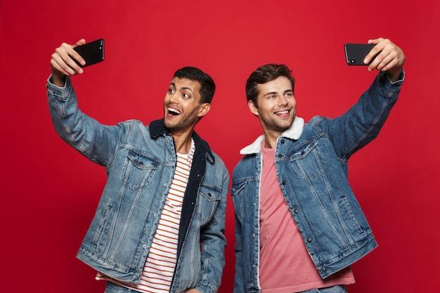 Двое веселых молодых людей, стоящих изолированно над красной стеной, делают селфи