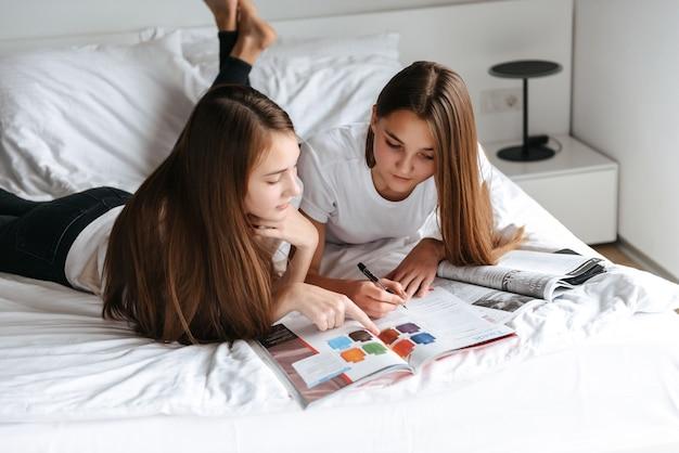 두 명랑 한 젊은 십 대 소녀 침대에 누워 잡지를 읽고