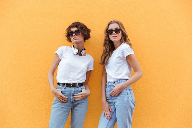 Two cheerful young teenage girls in sunglasses posing