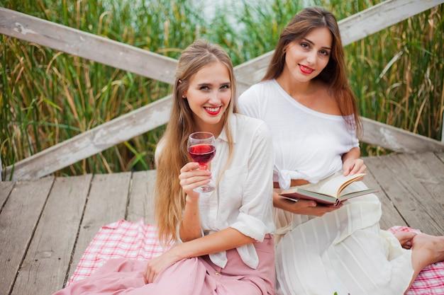 2人の陽気な若い女性は、夏の日に屋外でピクニックをします。