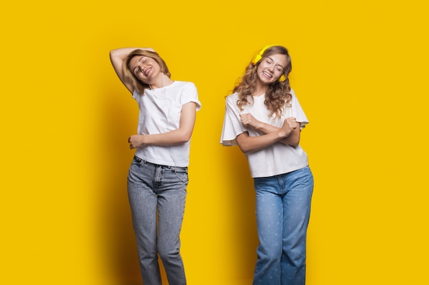 Two cheering sisters are listening to music using headphones and dancing on a yellow wall