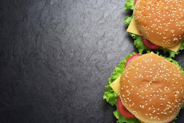 Two cheeseburgers on black slate wall