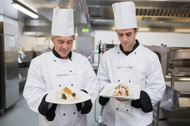 Two chef's looking down at their dishes