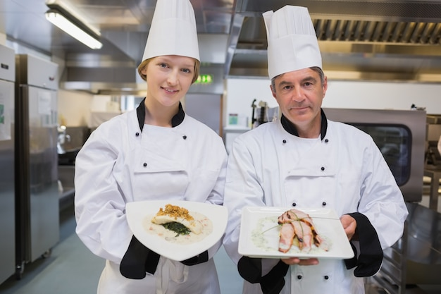 Two chef's presenting their dishes