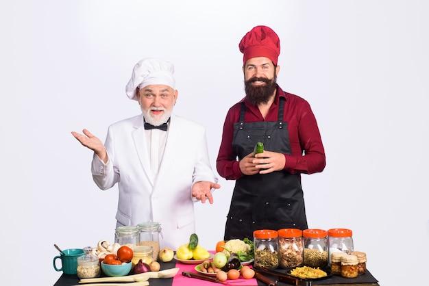 キッチンエプロンひげを生やした男のシェフを制服で調理する2人のシェフ