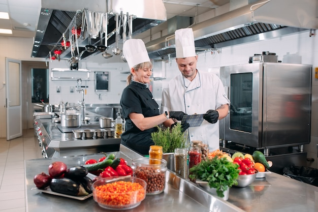 Two chefs discuss the menu in the kitchen of a restaurant