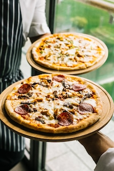 Two chefs holding italian pizzas on bamboo platters in front of the window