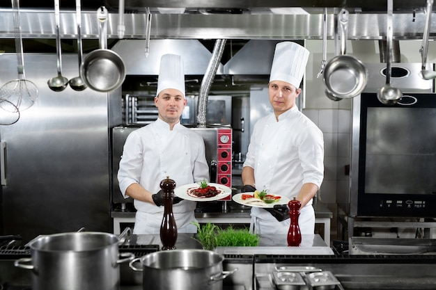 Two chefs in a professional kitchen hold ready-made dishes in their hands