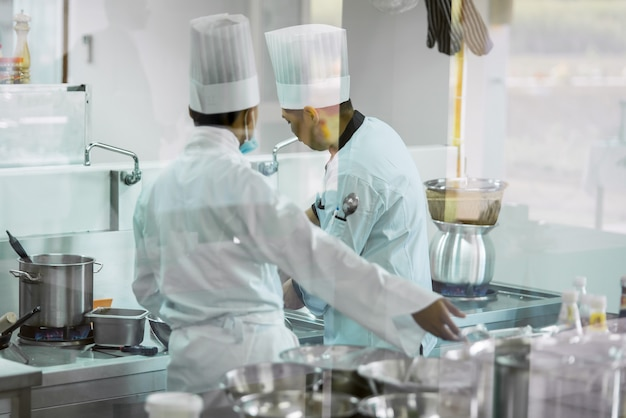 Два повара, которые готовят в белой форме от шеф-повара собираются готовить на кухне, чтобы подать еду клиентам в ресторане отеля