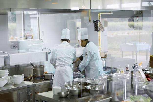 흰색 요리사 유니폼을 입고 요리하는 두 요리사 주방에서 요리를 시도하여 호텔 레스토랑에서 고객에게 음식 제공