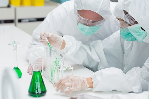 Two chemists adding green liquid to test tubes