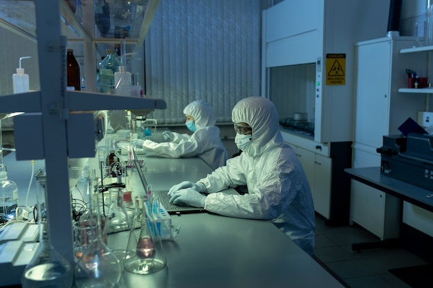 Two chemists in protective workwear sitting at the table and working on computers in the laboratory