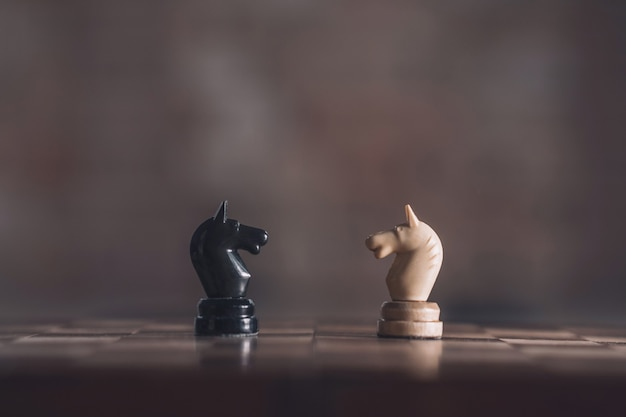 Two chess knights white and black standing opposite each other on vast blurred