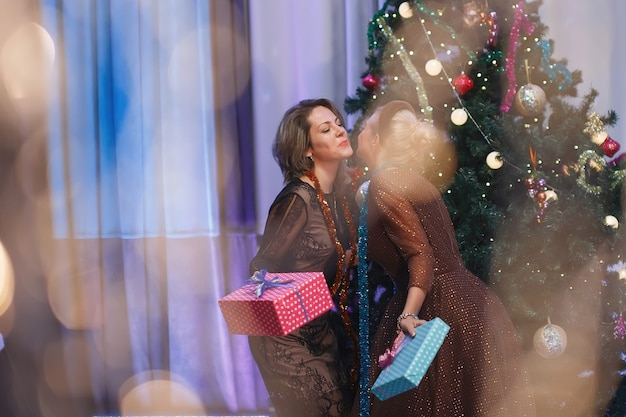 Two chic women rejoices with a gift box near a christmas tree. a woman laughs, smiles, poses. special vintage noise and grain filter, blurry lights.