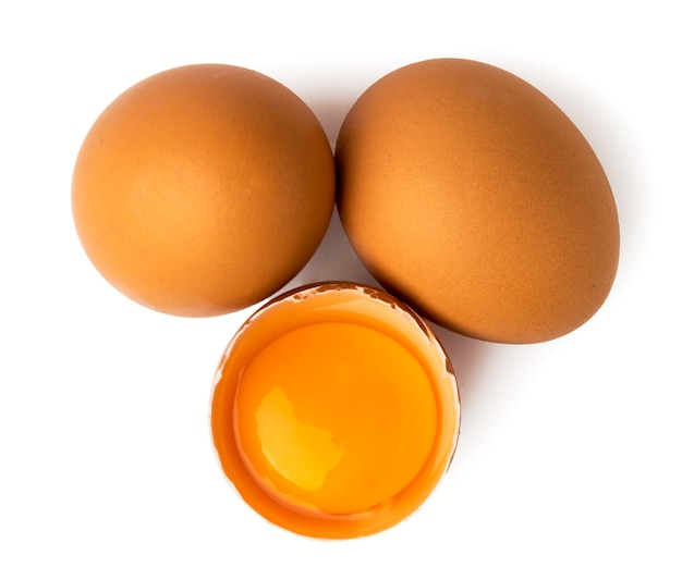 Two chicken eggs and broken egg on white. top view.