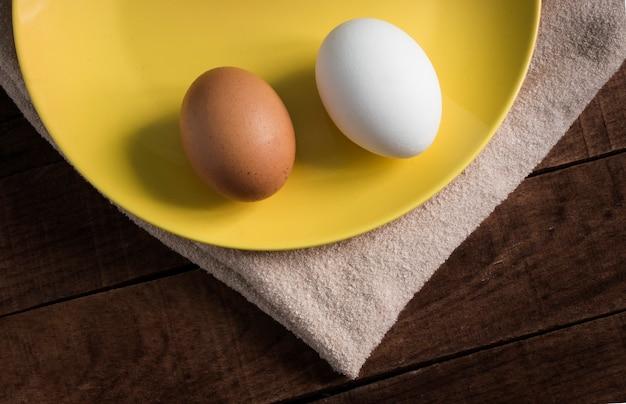 木製の背景の黄色いプレートに2つの鶏卵。