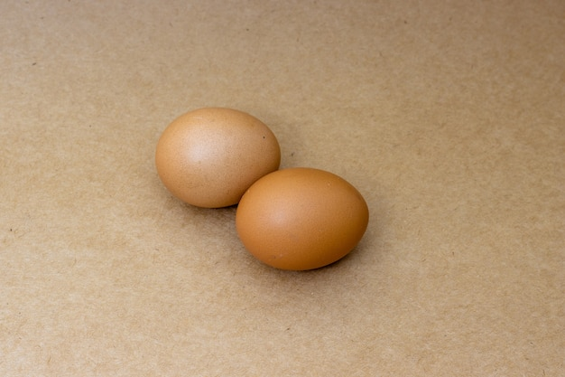 Two chicken eggs isolated on coconut wood surface