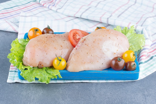 Два куриных филе на синей тарелке.