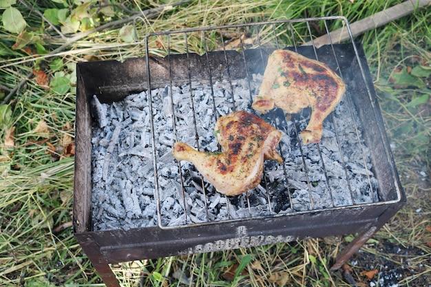Две куриные ножки жарятся на мангале