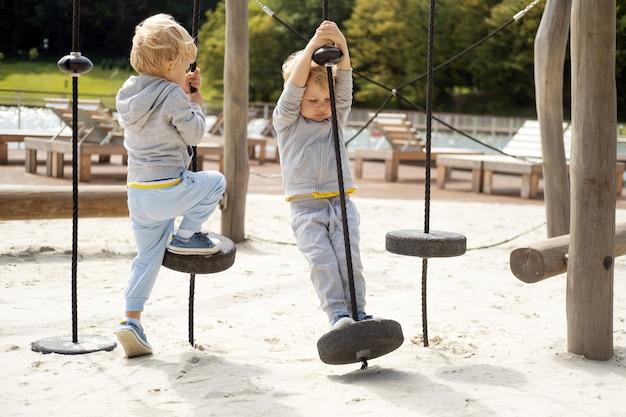 화창한 가을 날 어린이 놀이터에서 두 명의 소년 쌍둥이 형제가 놀고 있습니다.