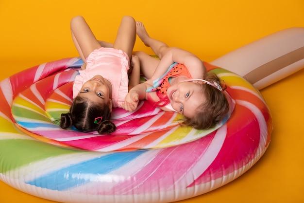 黄色の背景にカラフルなインフレータブルマットレスロリポップを楽しんで横たわっている水着の2人の子供の女の子。