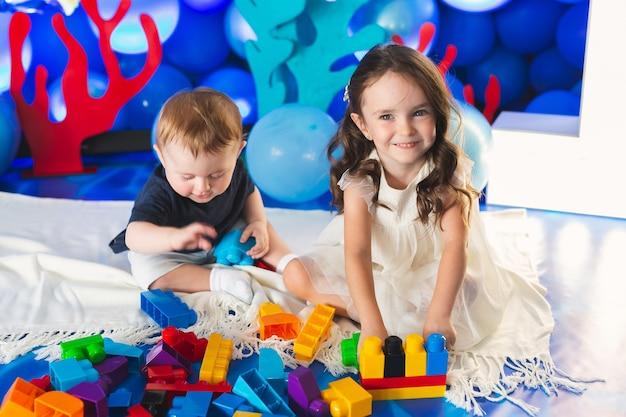 소년과 소녀 두 아이가 방 바닥에 앉아 웃고 놀고 있습니다.