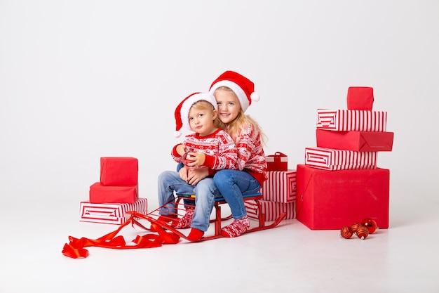 두 아이 소년과 스웨터와 모자에 소녀 산타는 선물을 운반하기 위해 썰매에 앉아있다. 스튜디오, 흰색 배경, 텍스트를위한 공간