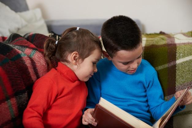 두 아이, 어린 소년과 소녀는 가족 사진 앨범을보고 서로 가까이 앉아. 형제와 자매