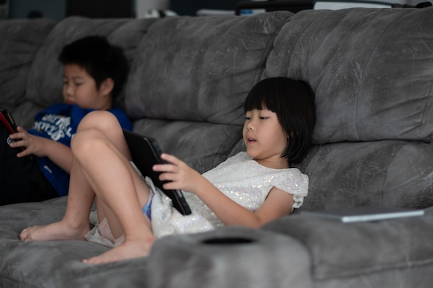 Two children addicted tablet, asian kid watching cartoon