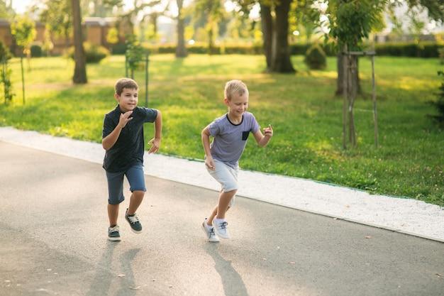 Двое детей играют в парке. два красивых мальчика в футболках и шортах веселятся, улыбаясь