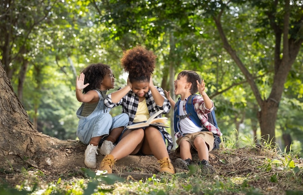 Двое детей кричат на ее сестру, пока сестра читает книгу
