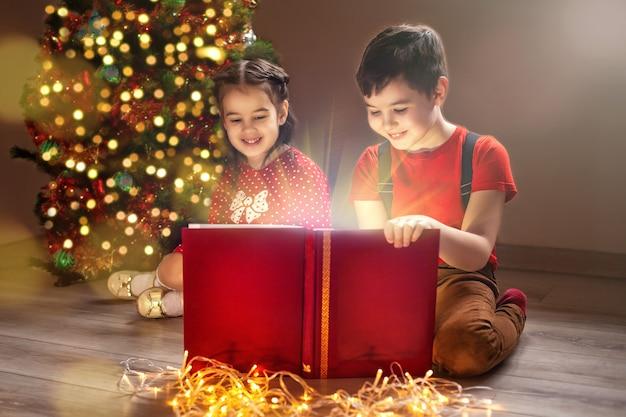 新年の木の近くに座って、本を見ている2人の子供