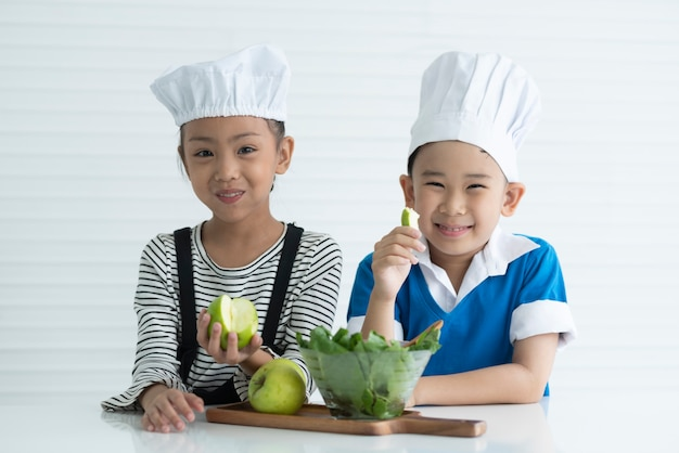 Two children boy and girl in cooking and kitchen concept