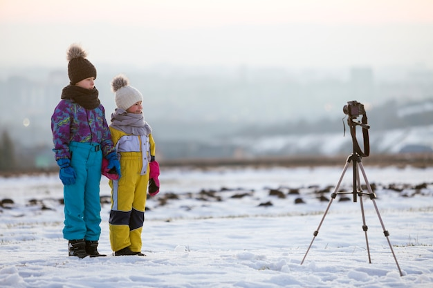 Two children boy and girl having fun outside in winter playing with photo camera on a tripod on snow covered field.