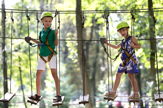 Two children, boy and girl in protective harness and safety helmets at climbing activity on rope way.