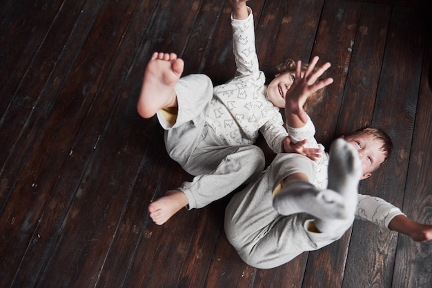 Двое детей, брат и сестра в пижаме играют вместе