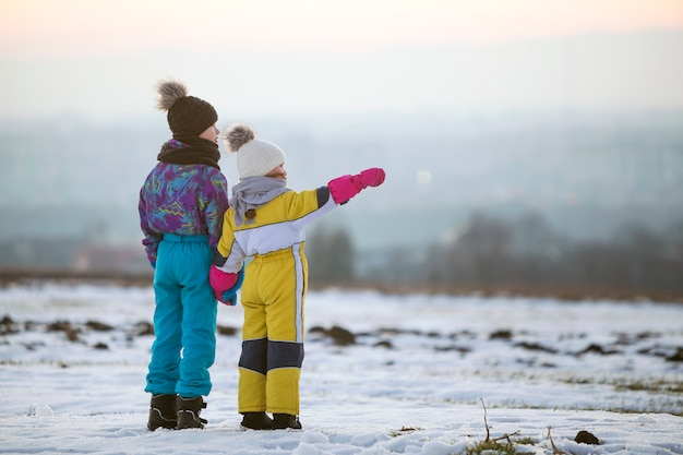 Two children brother and sister standing outdoors on snow covered winter field holding hands.