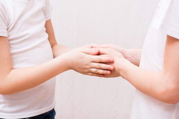 Двое детей осторожно держат друг друга за ладони