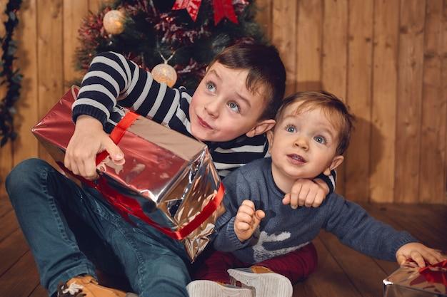 木製の背景を持つ彼らのクリスマスプレゼントで部屋で遊んでいる2人の子供を捕まえた