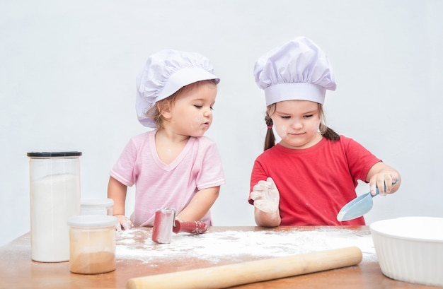 Two children in chef's hats are playing with flour. elder girl shows the baby the action